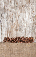 Burlap textile with coffee beans on the old wood