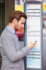 Businessman At Bus Stop With Mobile Phone Reading Timetable