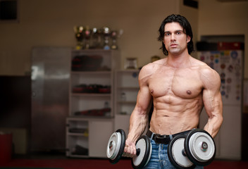 Shirtless muscular man holding weights (two dumbbells)