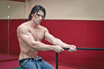 Handsome shirtless muscular man pulling rope
