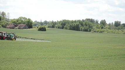 work with field equipment spraying fertilizer on the crop