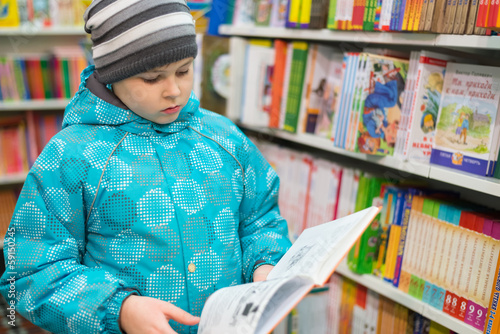 The boy chooses a book in the shop