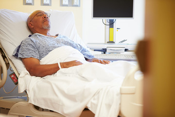 Senior Male Patient Resting In Hospital Bed