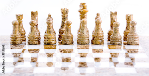 Stone made chess set over white background