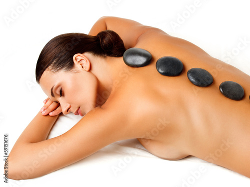Stone Massage. Beautiful Woman Getting Spa Hot Stones Massage