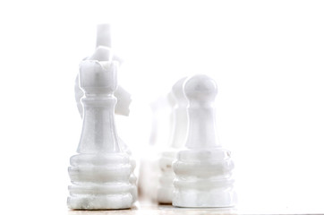 Stone made chess pieces over white background