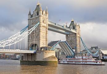 Tower Bridge open and boat passing through, London, England, UK