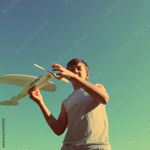 asian boy running airplane model - vintage retro style
