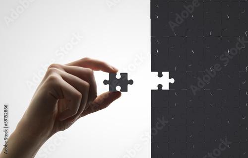 hand puts puzzle - 59152866