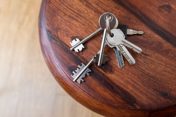 Bunch of keys lying on a wood shelf at the entrance