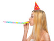 Profile portrait of girl in cap blowing in party horn blower