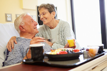 Senior Couple In Hospital Room As Male Patient Has Lunch