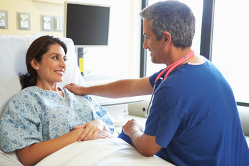 Male Nurse Talking With Female Patient In Hospital Room