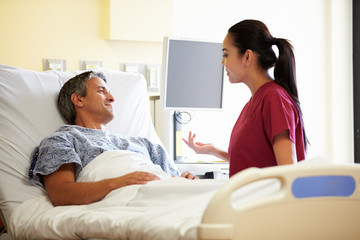 Nurse Talking To Male Patient In Hospital Room
