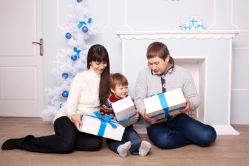 Young family holding gifts near the fireplace