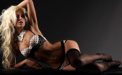 Sexy blonde young woman lying on a bench in wite black lingerie