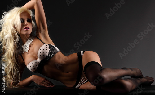 canvas print picture Sexy blonde young woman lying on a bench in wite black lingerie