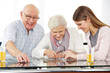 Social worker solving jigsaw puzzle with senior couple