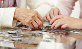 Old hands solving jigsaw puzzle