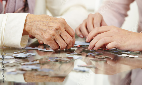 Old hands solving jigsaw puzzle - 59157661