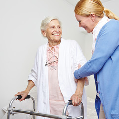 Geriatric nurse helping senior citizen woman