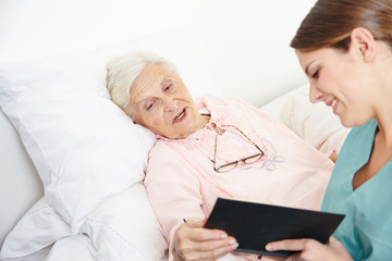 Geriatric nurse reading book to senior woman