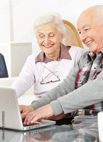 Senior couple chatting over internet with computer