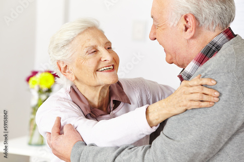 Two senior citizens dancing and smiling