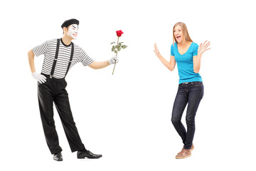 Mime artist giving a rose flower to an excited woman