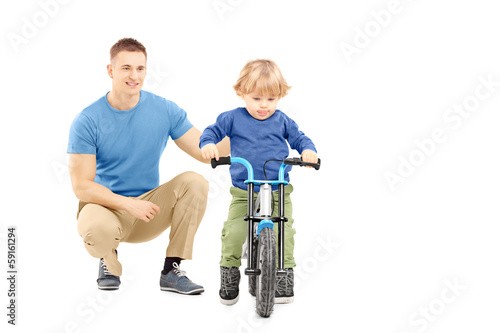 Father near his son trying to ride a bicycle