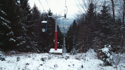 Ski lift on the slope between the trees