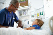 Young Girl Talking To Male Nurse In Intensive Care Unit