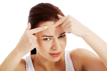 Young woman is pimpling spot on forehead.