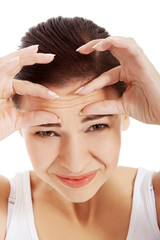 Young beautiful woman is checking her wrinkles on forehead.