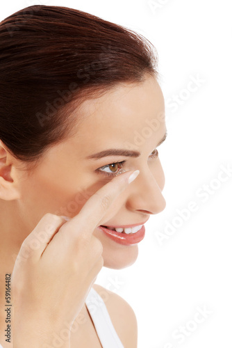 Young beautiful woman putting contact lens.