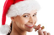 Beautiful woman in santa hat eating a cookie.