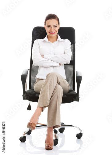 Beautiful happy business woman sitting on a chair.