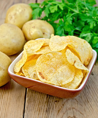 Chips in a bowl with a potato on the board