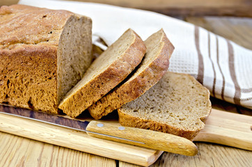 Rye homemade bread sliced on the board with a napkin