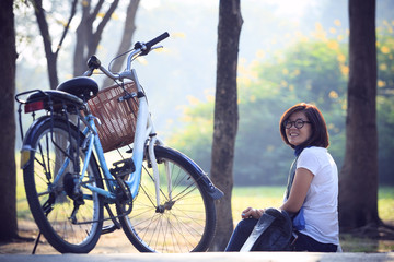asian woman sitting in the park with bicycle in morning