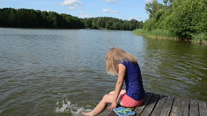 girl sitting on bridge large lake slosh water feet sunny day