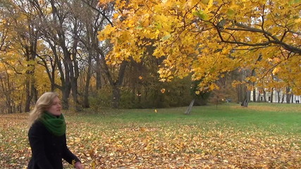 woman shake yellow leaves dressed tree branch in park
