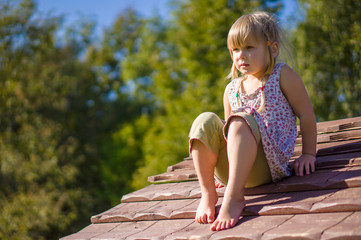 Adorable girl sit on kids house roof on playground
