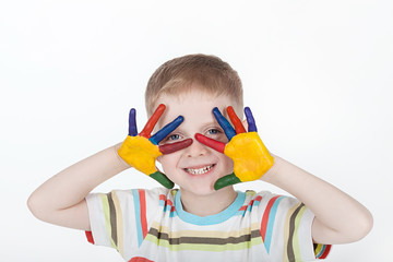 smiling boy with hands in paint on a white background