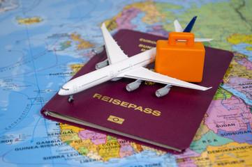 Flugzeug mit Reisepass und Koffer