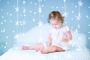 Adorable baby girl with curly hair playing star lights on a whit