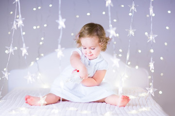 Sweet baby girl playing with a toy on a white bed betwen sparkli