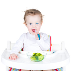 Portrait of a cute toddler eating broccoli in a white high chair