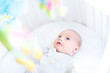 Cute newborn baby watching colorful toys in his white crib