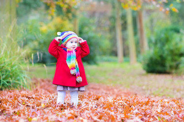 Little toddler girl playing in an autumn park with maple leaves
